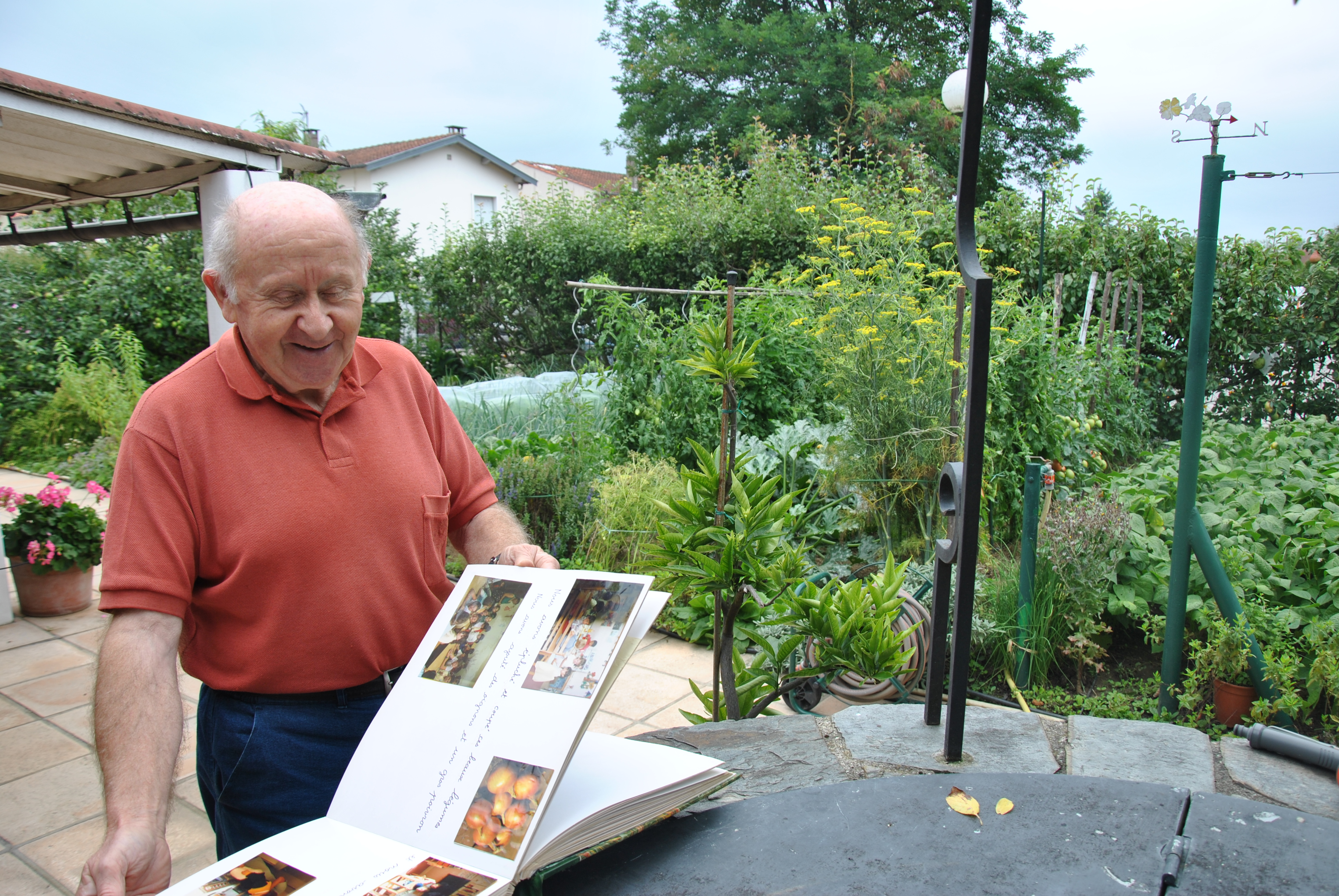 René Guiraud feuilletant le grand livre-souvenir de son jardin d'école.